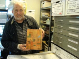 Bob is holding a map from 1883, before Cochran's time, showing where the Bryn Mawr train station was going to go.